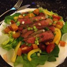 steak spread over salad, fresh salad with steak, juicy steak and salad
