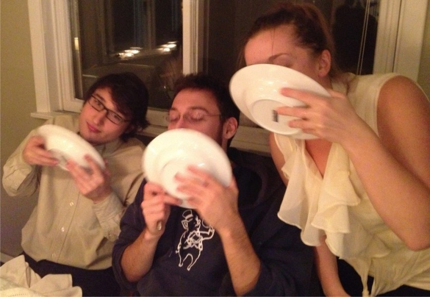 Three kids licking their soup bowls clean