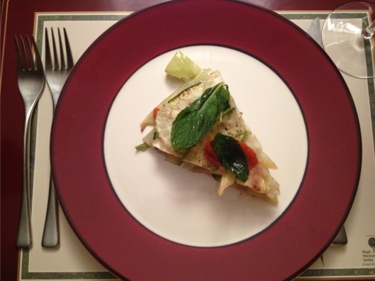 A serving of zucchini fennel and red pepper torta with mint on a plate.