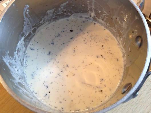 Heating heavy cream with vanilla beans in a pot.