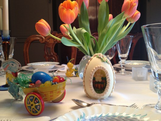 Easter table set with sugar eggs, orange tulips and antique Easter toys.