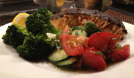 Sesame curry crusted salmon with steamed broccoli and tomato cucumber salad on a white Wedgewood plate.