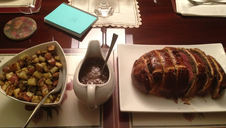 Father's Day dining table of Tyler Florence's Beef Wellington, Green Peppercorn Sauce, and Herb and Garlic Roasted Potatoes.
