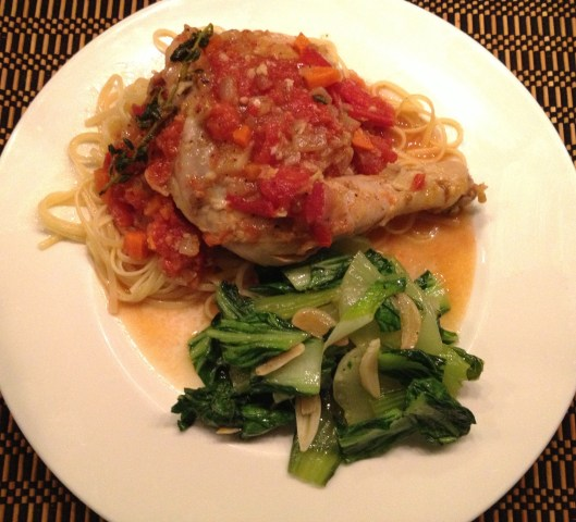 Tomato chicken braise on a plate with sauteed baby bok choy.