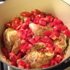 Browned chicken covered with chopped tomatoes in a pot.