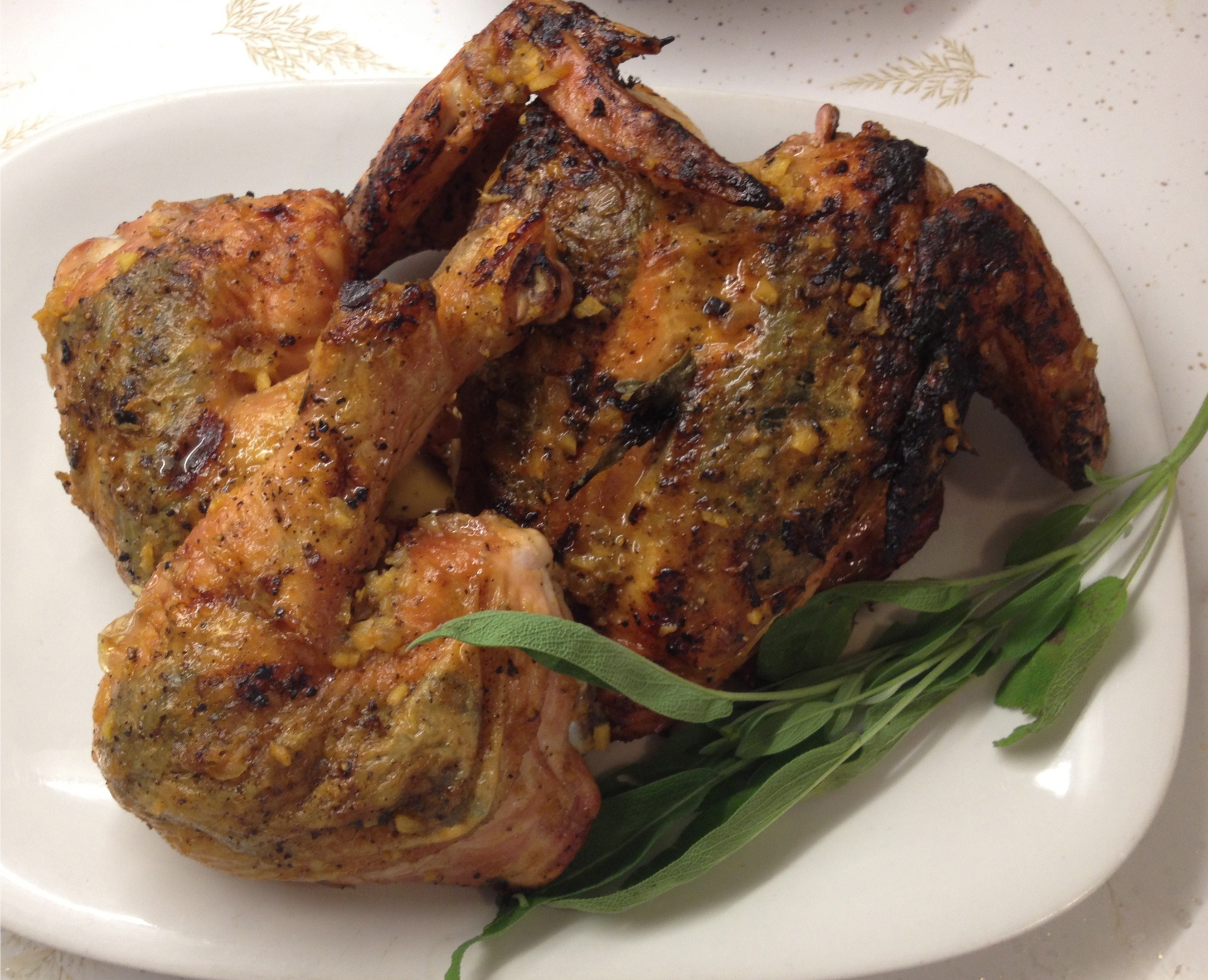 Grilled chicken with a Lemon Ginger Basting Sauce on a white platter with a stem of sage.