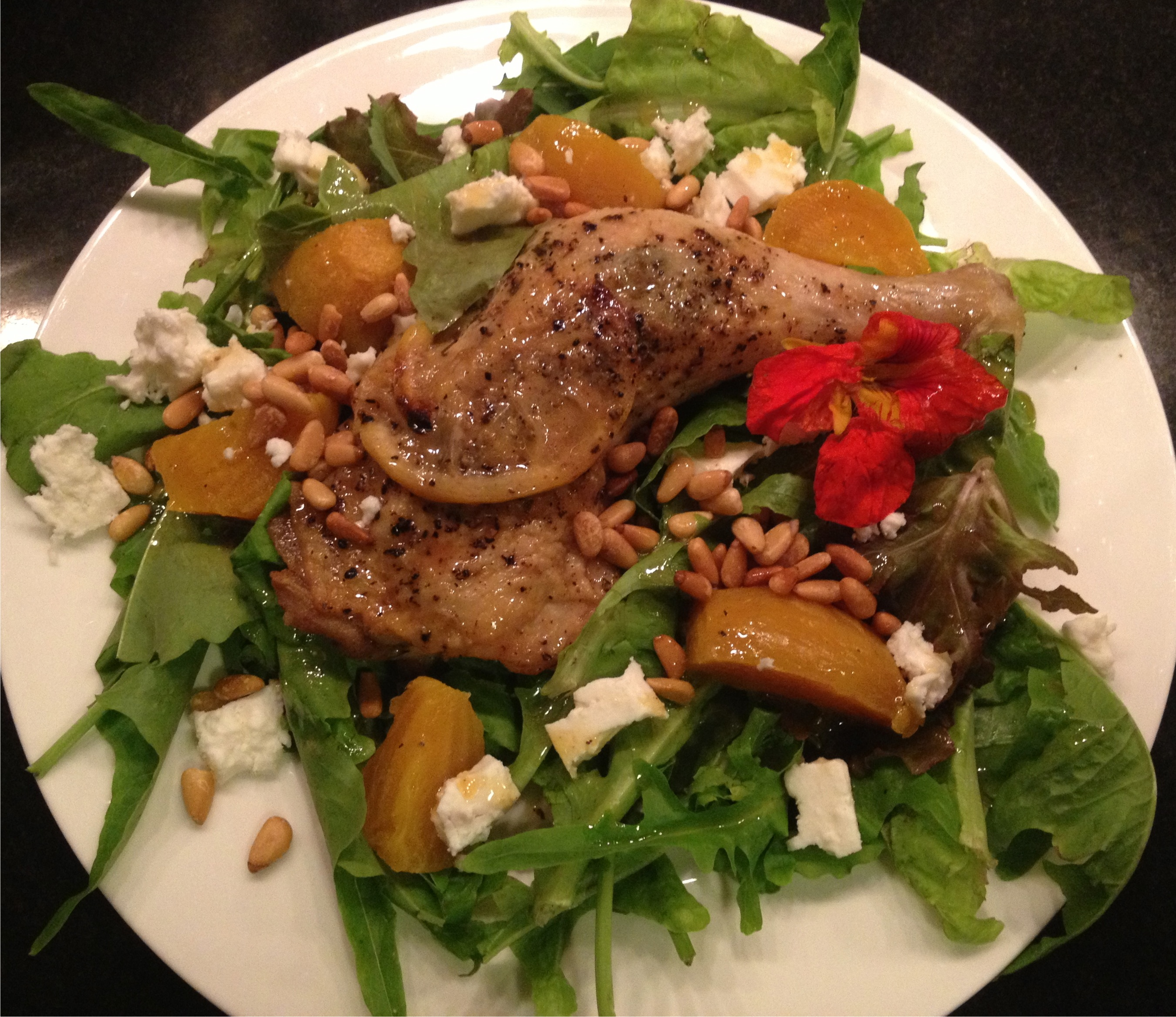 Dinner salad with roast chicken leg, roasted yellow beets, feta cheese and toasted pine nuts on a white Wedgewood plate, overhead shot.