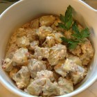Midwest potato salad in a white Le Crueset bowl garnished with parsley.