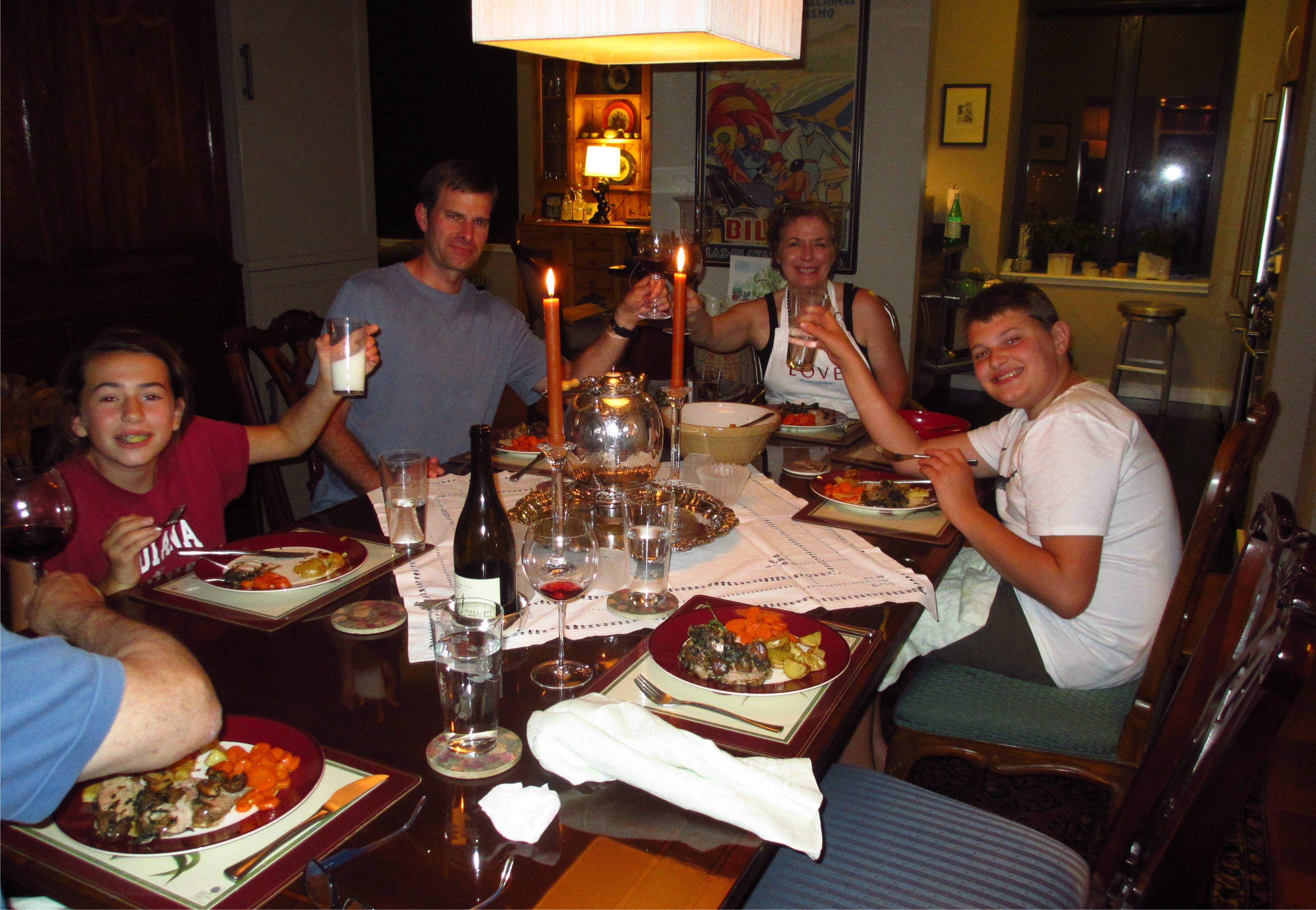 House guests  with a family toasting at the dinner table.