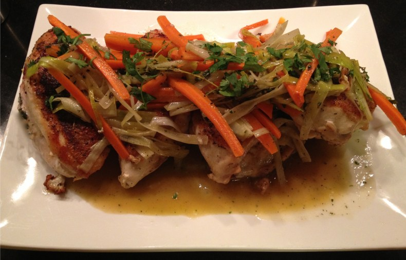 Pan roasted chicken breasts with carrots and leek, garnished with parsley on a white platter.