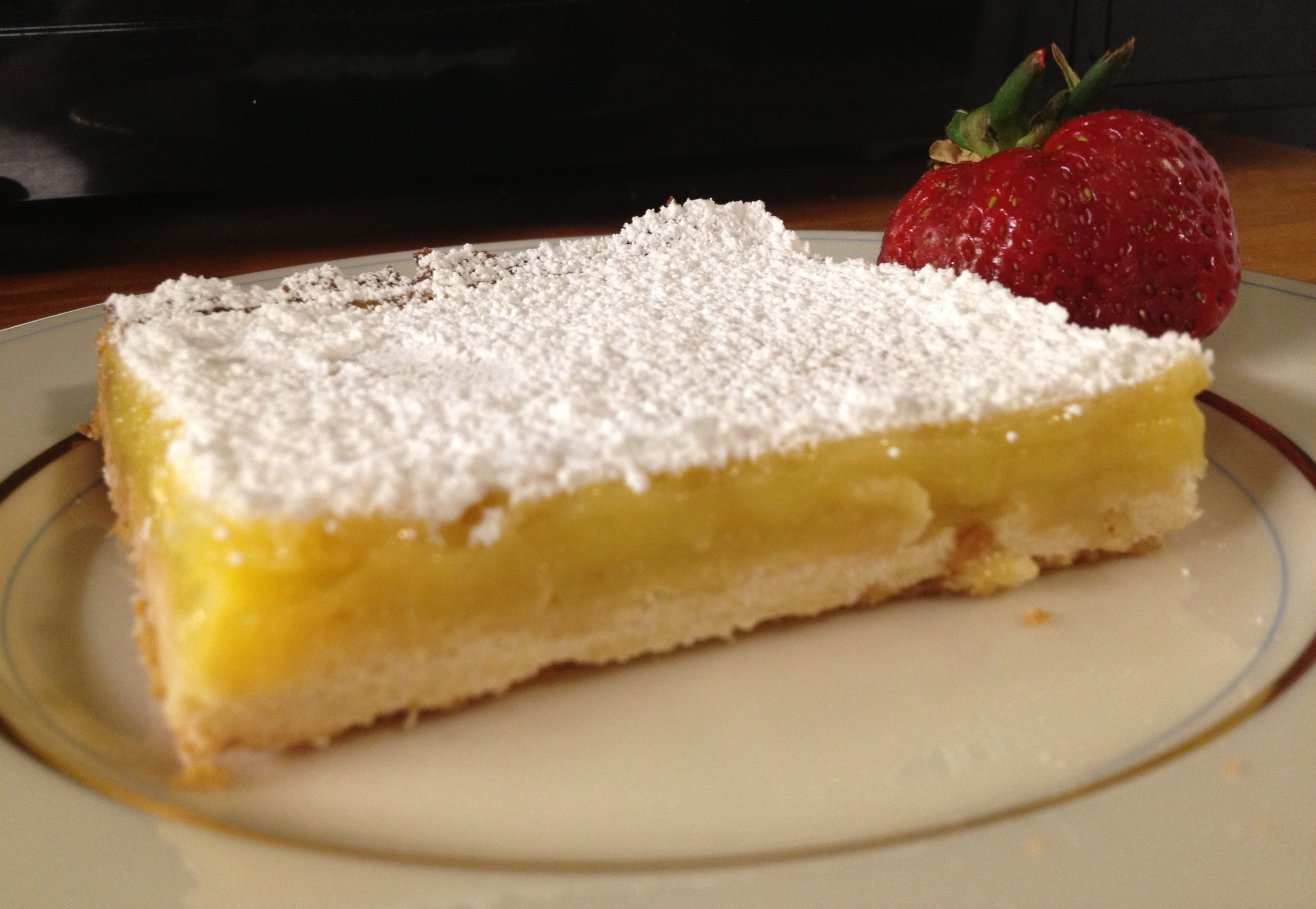 Lemon bars on a off white china plate with a fresh strawberry.