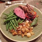 Dinner plate with Leg of Lamb, Nicoise tomatoes, haricot vert, and roasted potatoes.