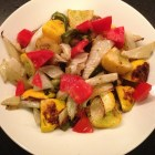 Roasted patty pan squash, fennel, green pepper and fresh tomato in a white serving bowl.