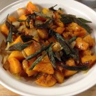 Butternut squash with crispy sage leaves in a white serving bowl.