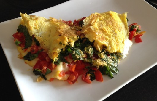 Omelette with two cheese, red pepper, tomatoes and basil.