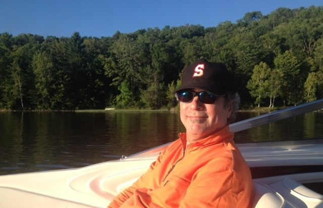 Man on a boat with a Summit NJ baseball hat on.