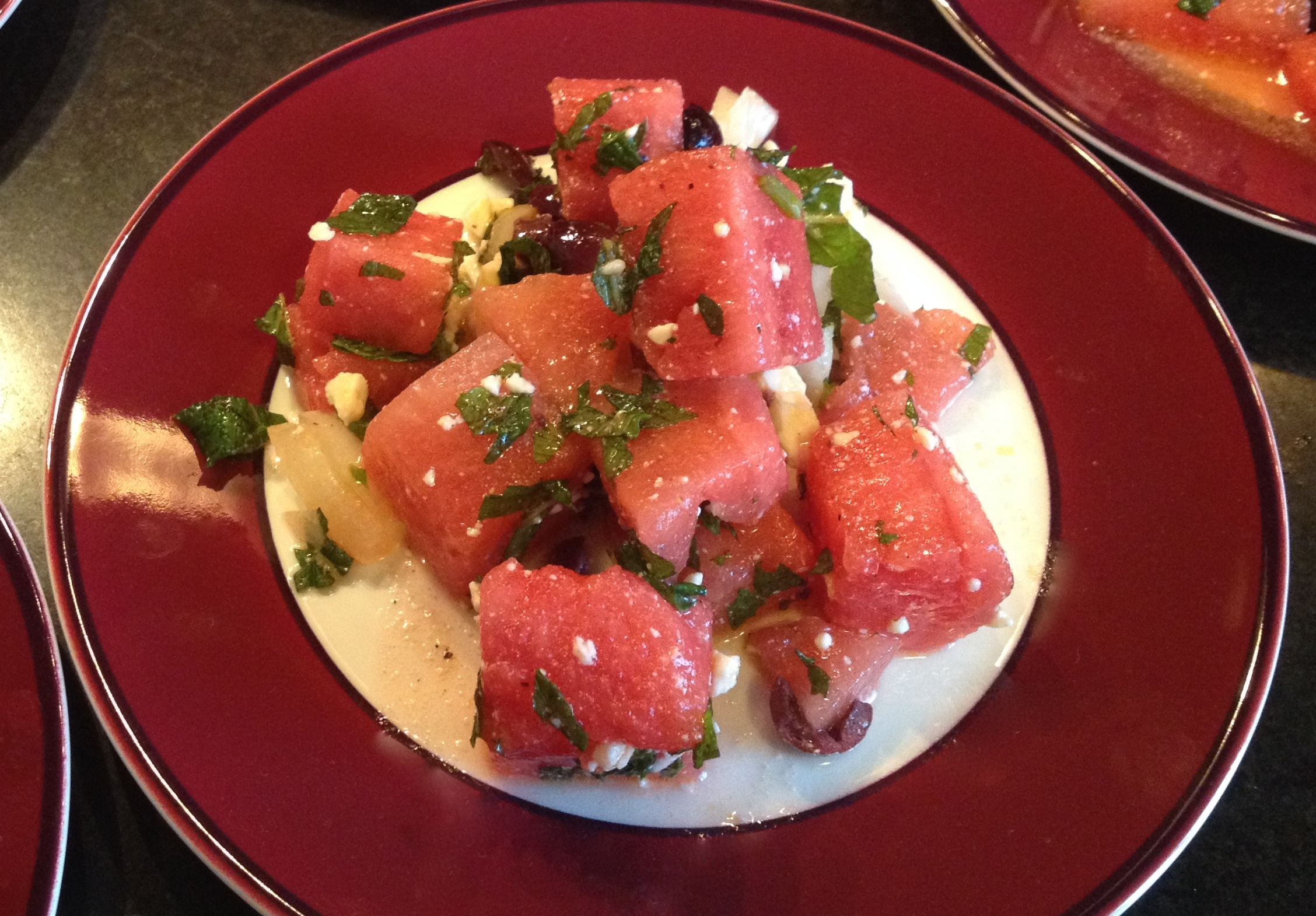 Watermelon salad with feta and mint on a burgundy trimmed plate.