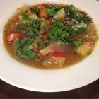 Vegetable soup in a white rimmed bowl.