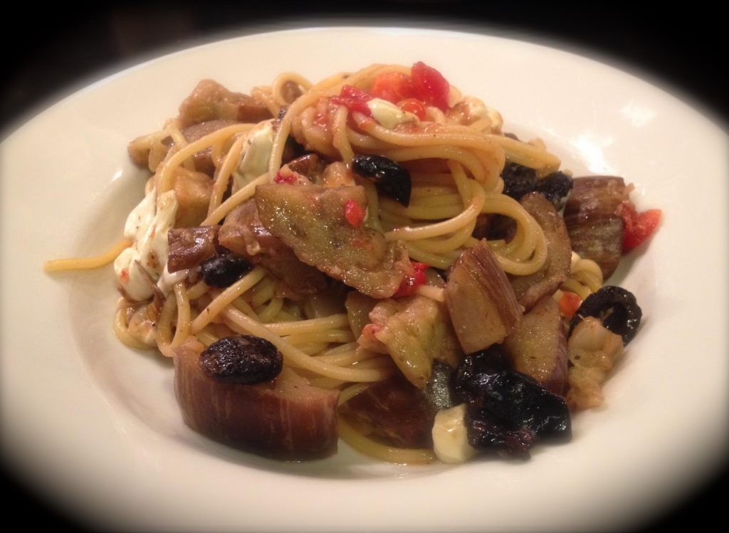 Eggplant mozzarella and oil-cured black olive spaghetti in a white bowl with blurred edges.