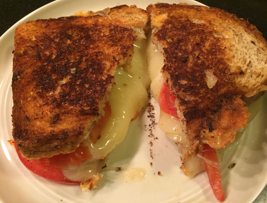 Provolone grilled cheese and tomato sandwich cut in half.