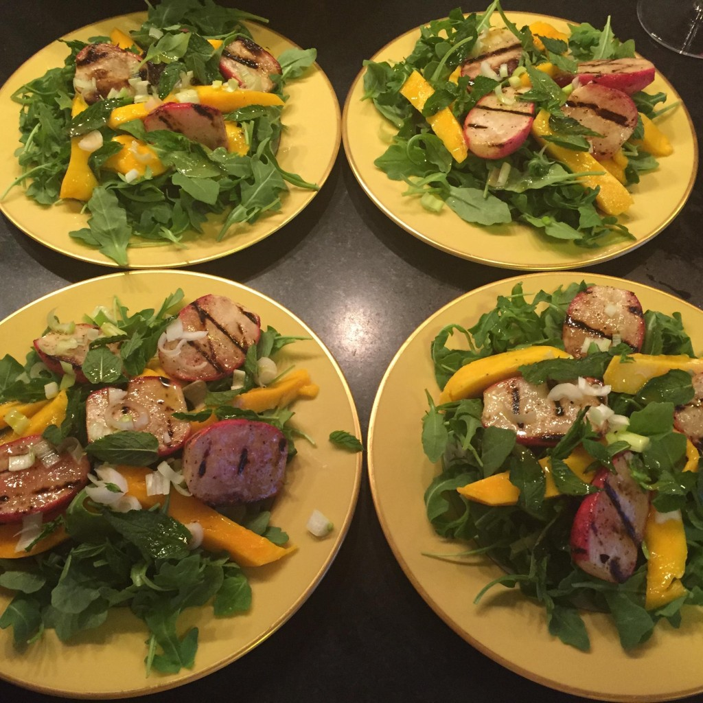 Baby arugula salad with grilled radishes, mango, mint and scallions on four yellow rimmed plates.