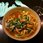 Curry pho with veal and veggies in a serving bowl.