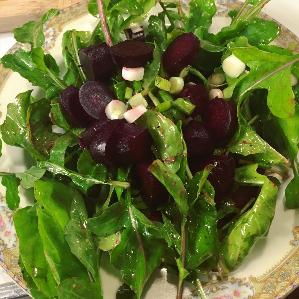 Arugula, roasted beet and scallion salad on an antique plate.
