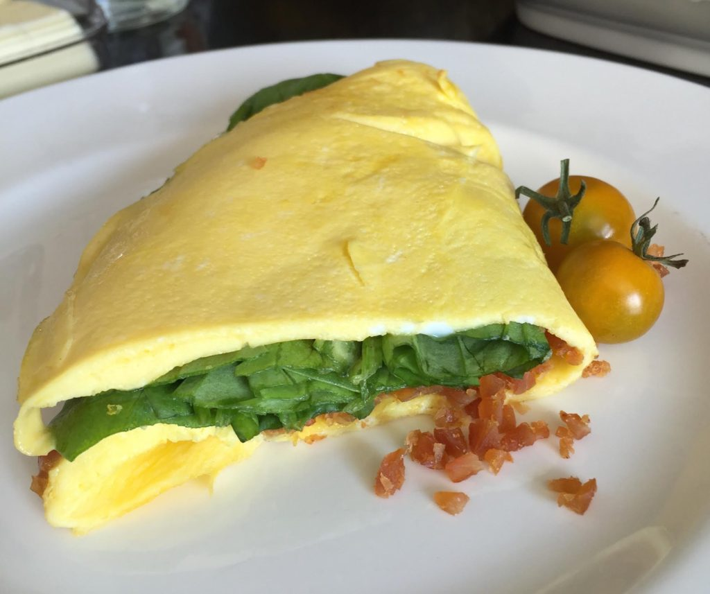 Chef's Cut Honey Barbeque Chicken Jerky & Spinach Omelet finished on a white Wedgewood plate.