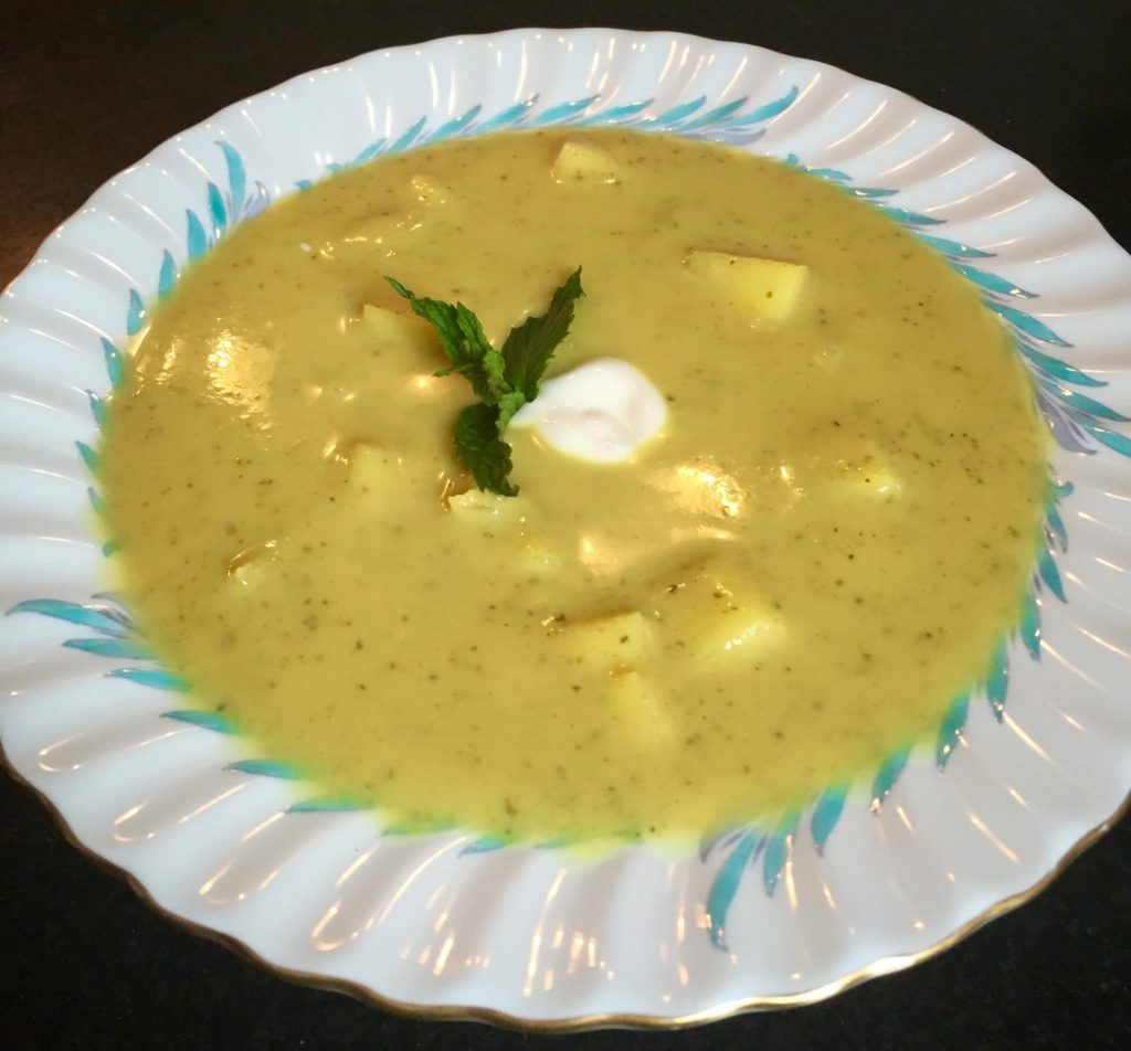 Chilled Curried Zucchini soup with apples, mint and yogurt garnish in a Limoges bowl.