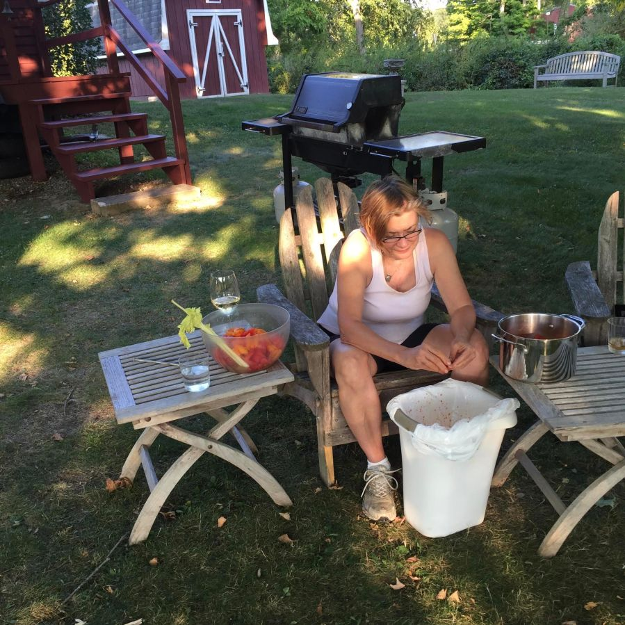 Woman deseeding fresh tomatoes outside in the yard.