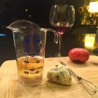 POURfect measuring beaker with Roquefort cheese, a tomato and a glass of wine.
