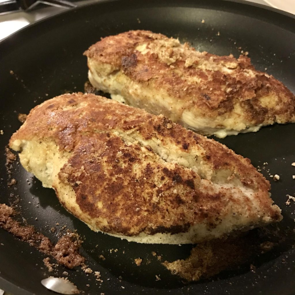 Almond flour on chicken breasts sauteing in a skillet.