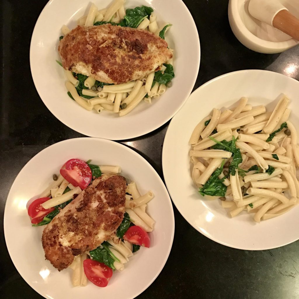 White bowls filled with pasta with baby spinach with almond flour breaded chicken breasts on top.