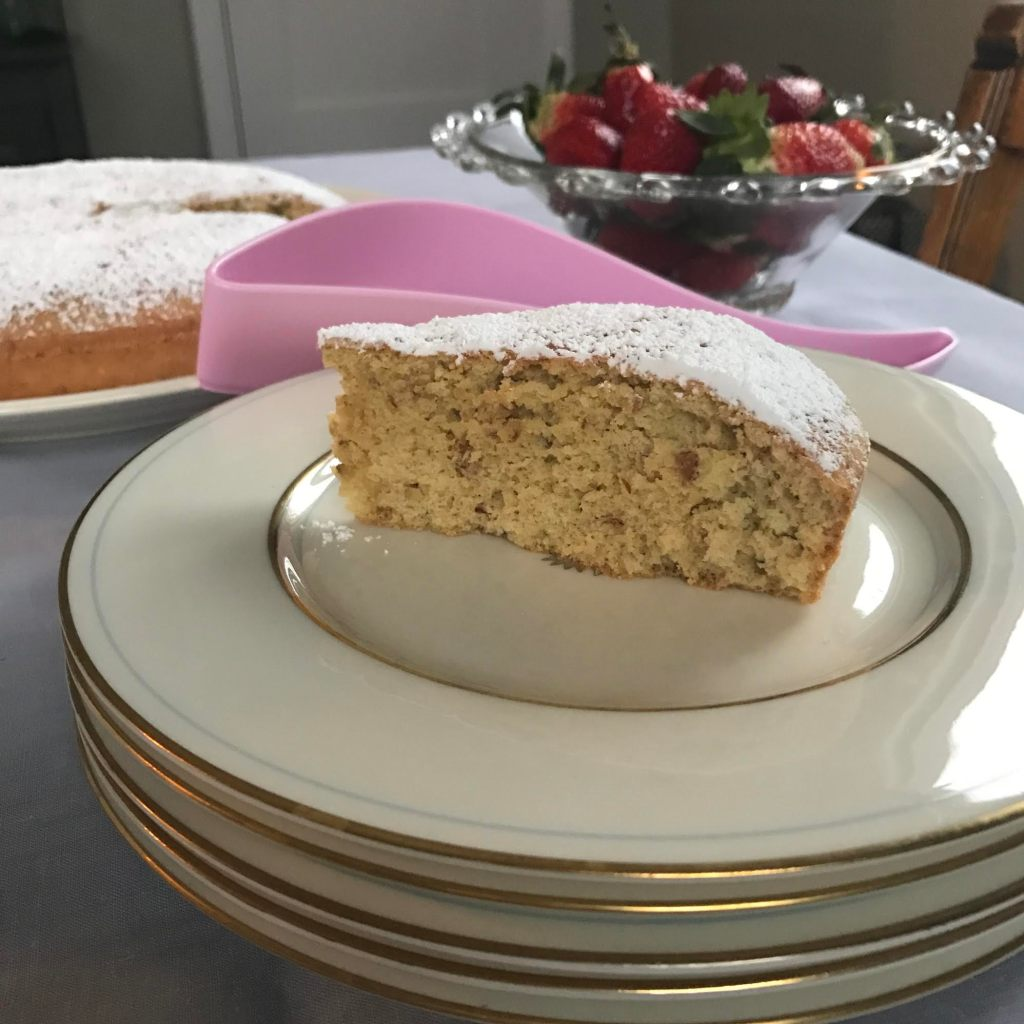 Slice of Pecan, Olive Oil and Benedictine coffee cake with strawberries in the background.
