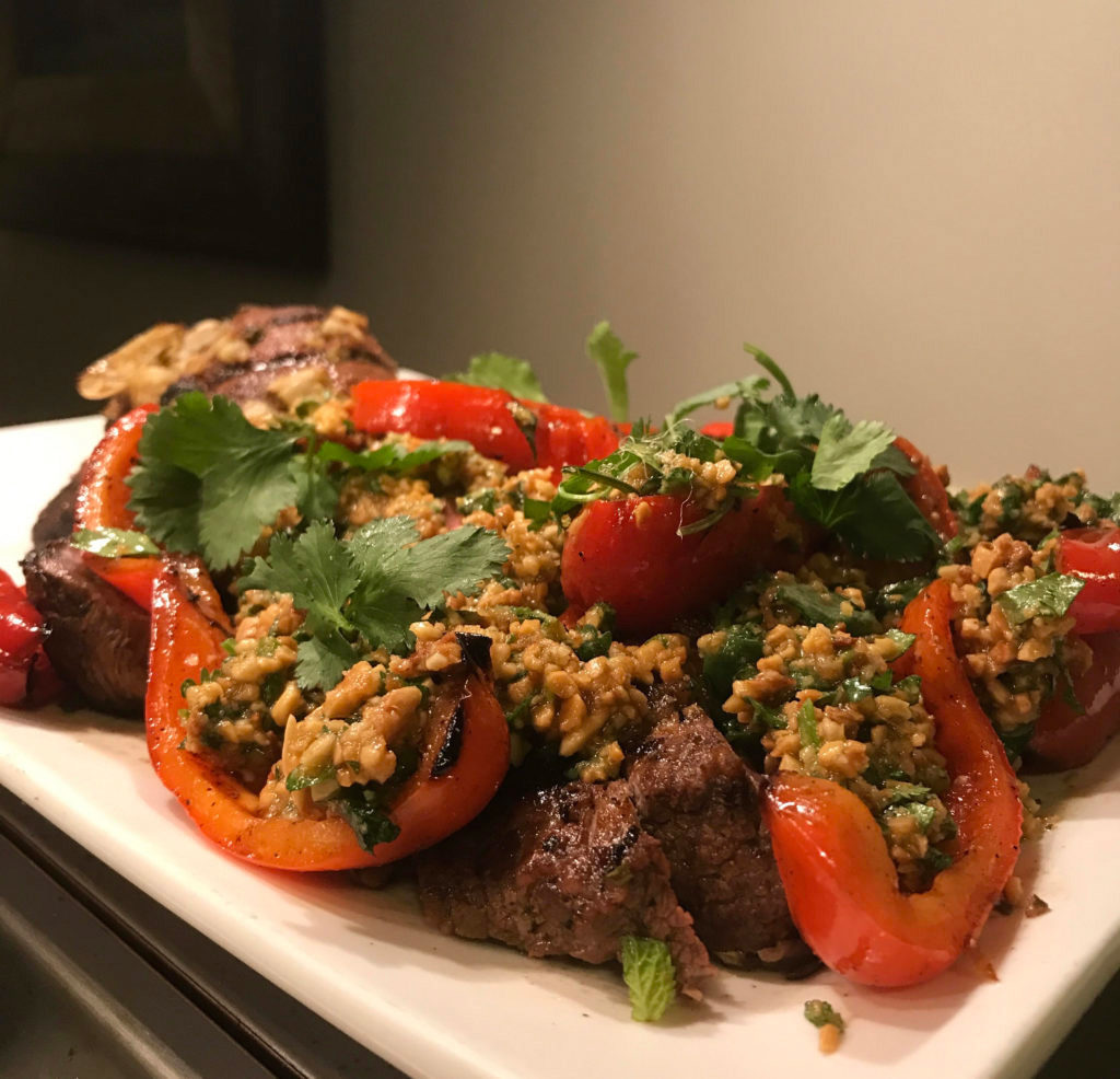 Ottolenghi Grilled Leg of Lamb recipe with red peppers and almond sauce on a white platter, garnished with cilantro.
