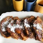 Buttermilk Challah French Toast on an antique white platter with powdered sugar and 3 cups of coffee.
