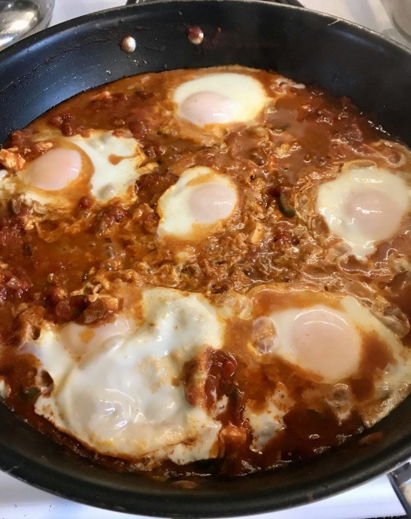 Shakshuka in skillet with cooked eggs.