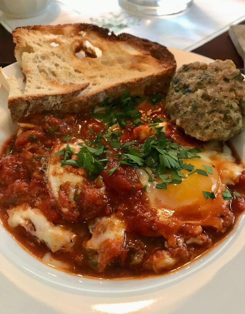 Shakshuka serving with sausage and bread.
