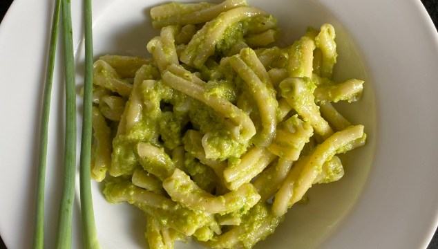 Garlic Scape Pesto Pasta in a white bowl, garnished by scapes.