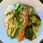Finished Salmon Rice Bowl with Ginger-Lime Sauce with a side of roasted broccoli.