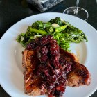 Pork Chops With Ginger Blackberry Sauce, on a white plate with a side of broccoli rabe.