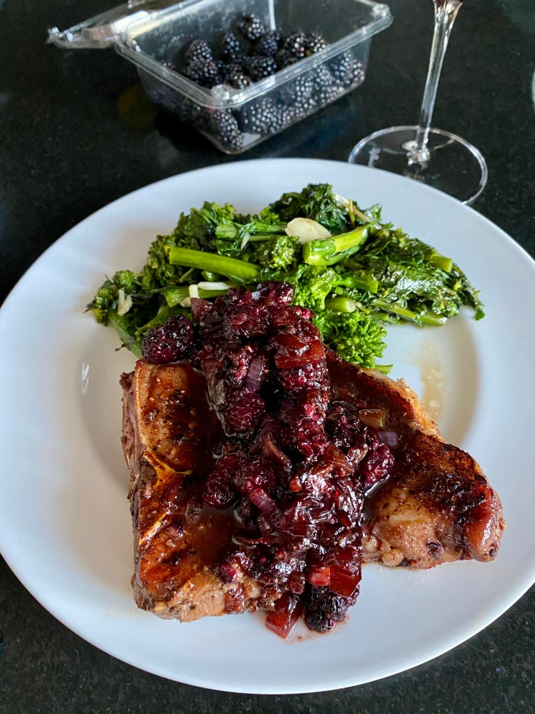 Pork Chops With Ginger Blackberry Sauce, finished on a white plate with a side of Broccoli Rabe.