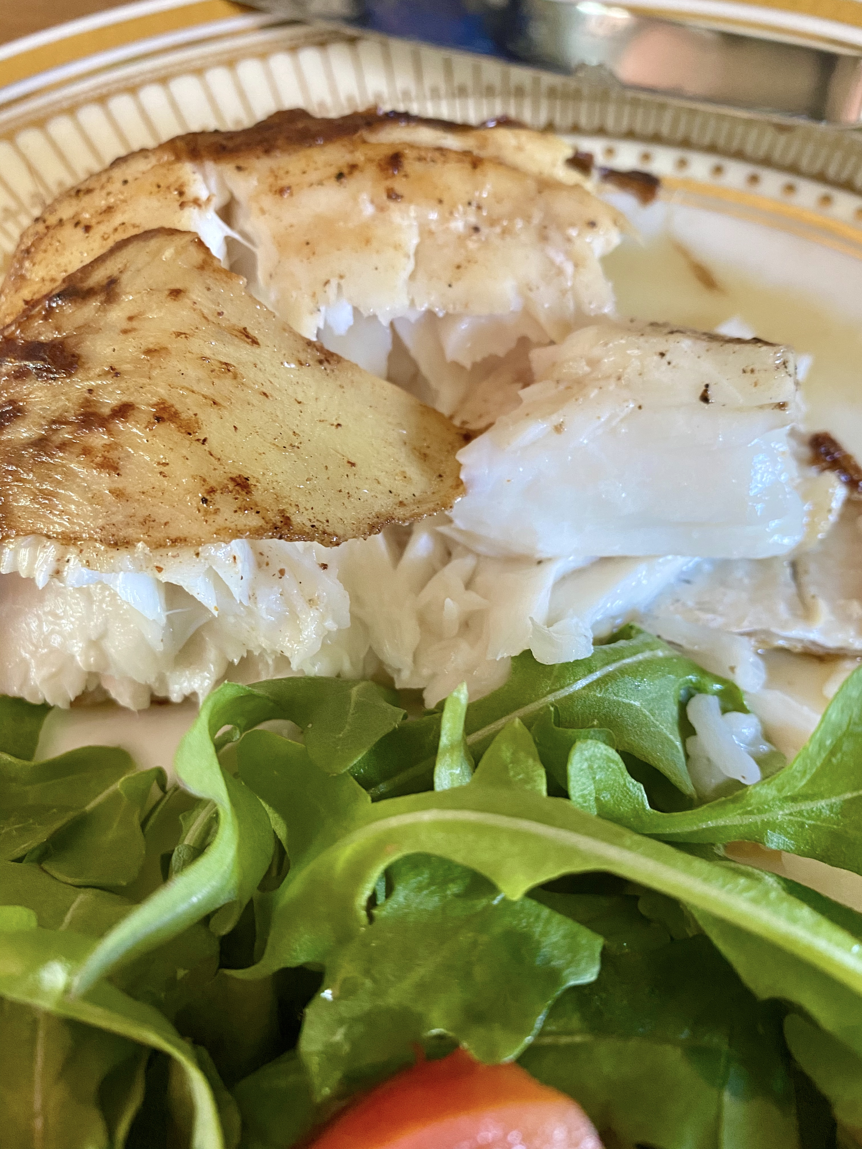 Ginger-crusted halibut cut with arugula and tomato salad.
