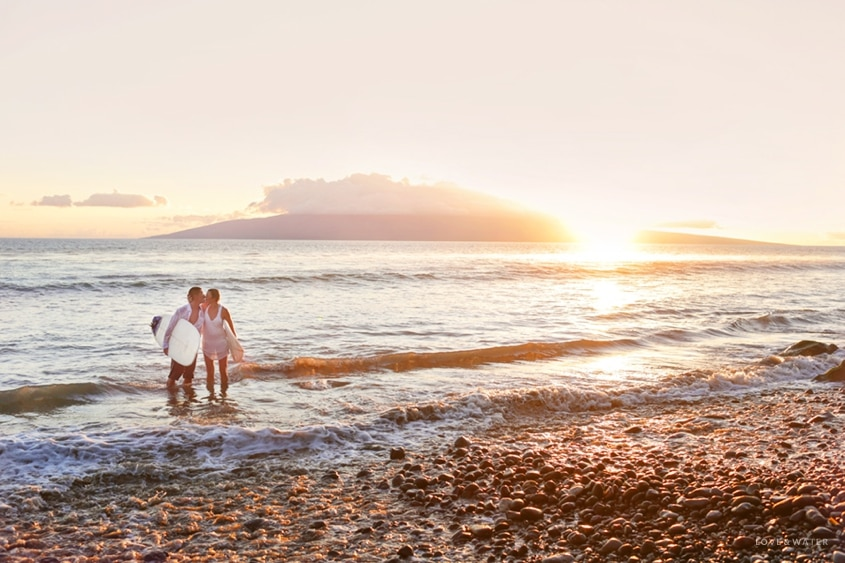 Maui surfboard elopement with Love + Water Photography shows newlyweds kissing in the water at sunset with their surfboards