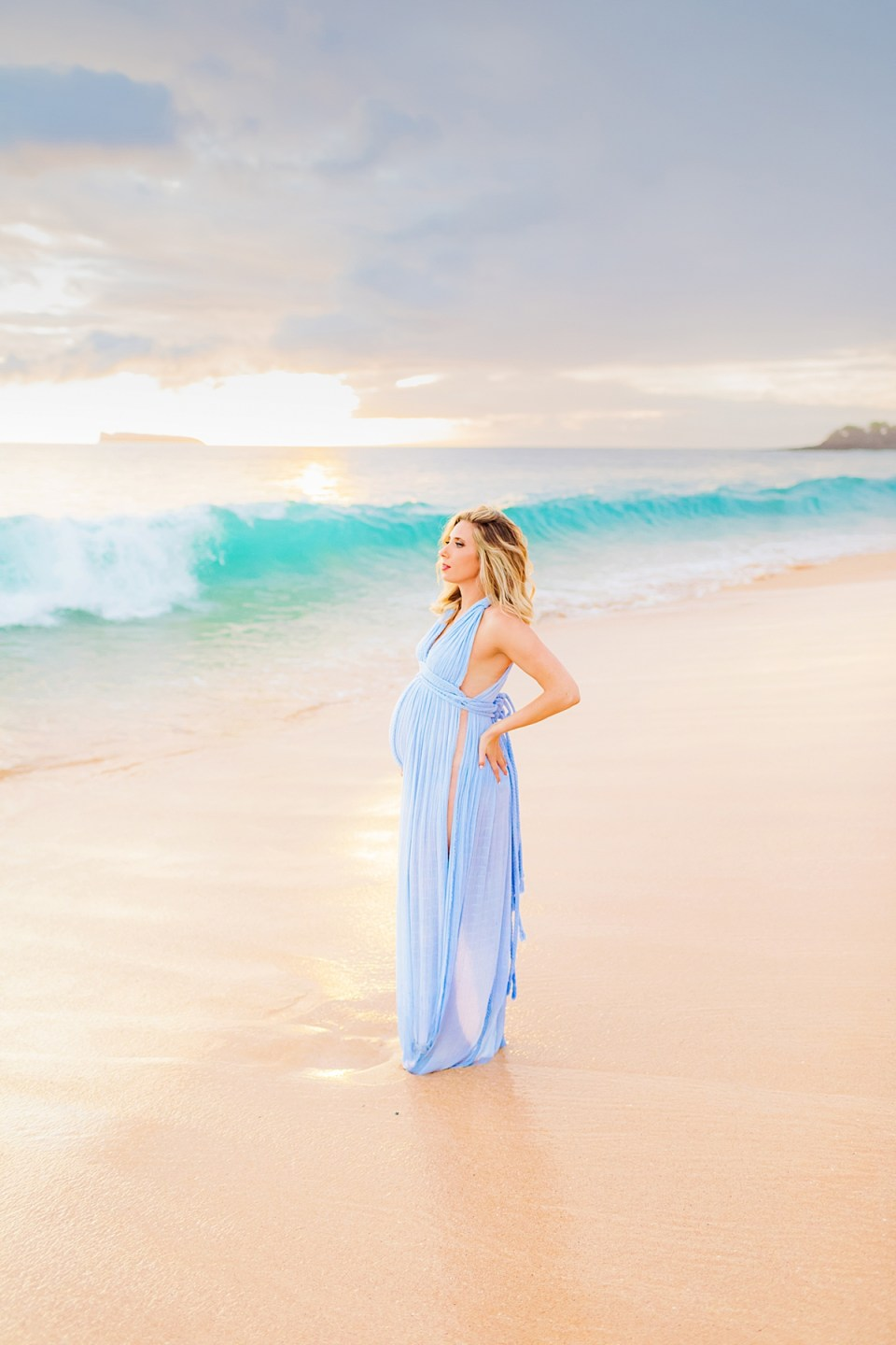 Pregnant woman in Wailea holding her hand to hip and looking out toward the ocean