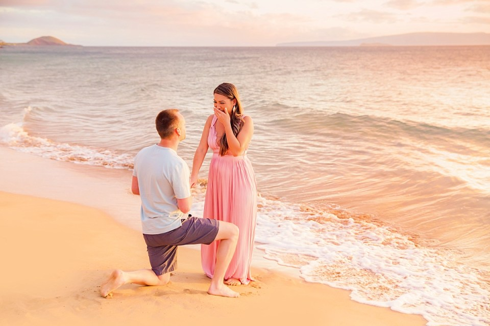 A woman in a flowing pink dress covers her mouth in happy surprise as a man proposes on the beach at sunrise in Hawaii.