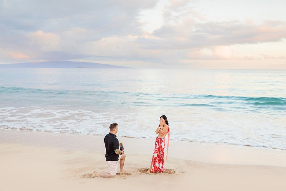 A woman in a beautiful long, floral skirt covers her mouth in surprise as her fiance proposes on the beach in Hawaii.