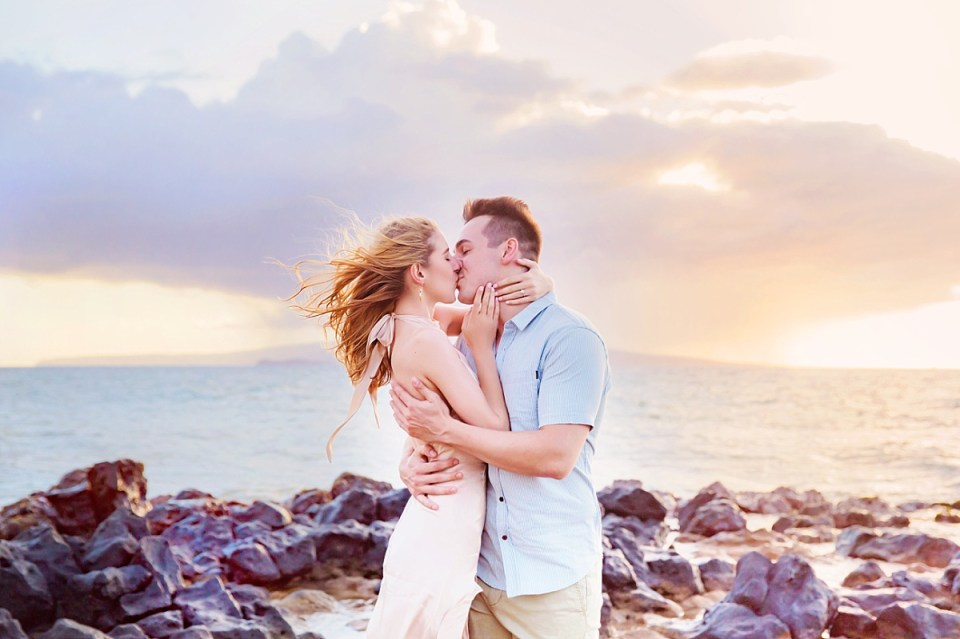 A beautiful couple holds each other and kisses in front of the ocean during a beach engagement session in Hawaii.