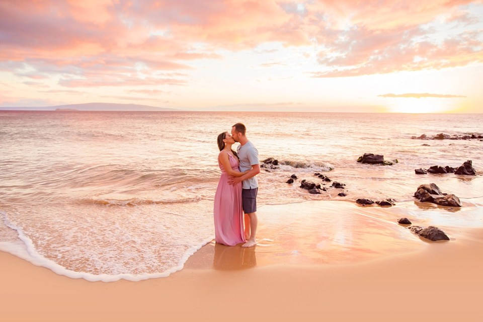 A newly engaged couple kisses on the beach during a surprise proposal photos session with Love + Water in Wailea, Maui, Hawaii.