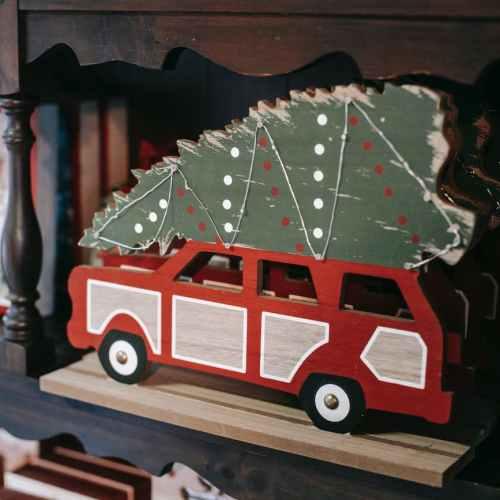 decorative christmas vehicle with fir tree on shelf